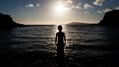 Silhouette of boy in sea