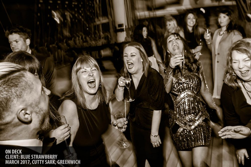 Guests laughing on the deck of the Cutty Sark at a corporate event photography copyright Paul Clarke